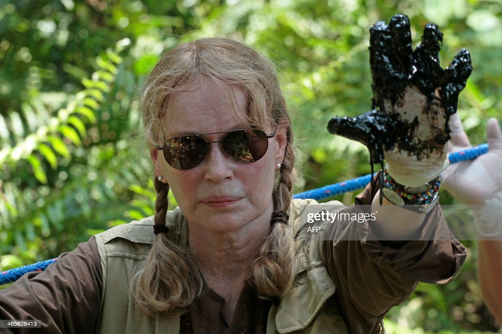 US actress Mia Farrow shows her left hand soiled with oil during a visit to an Amazonic area affected by pollution created by US oil company Chevron, in Lago Agrio, Aguarico, Ecuador, on January 28, 2014. AFP PHOTO/JUAN CEVALLOS