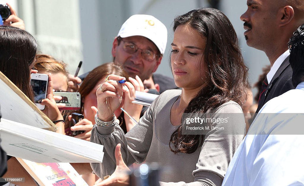 Actress Michelle Rodriguez signs autographs during ceremony honoring actor Vin Diesel on The Hollywood Walk of Fame on August 26, 2013 in Hollywood, California.