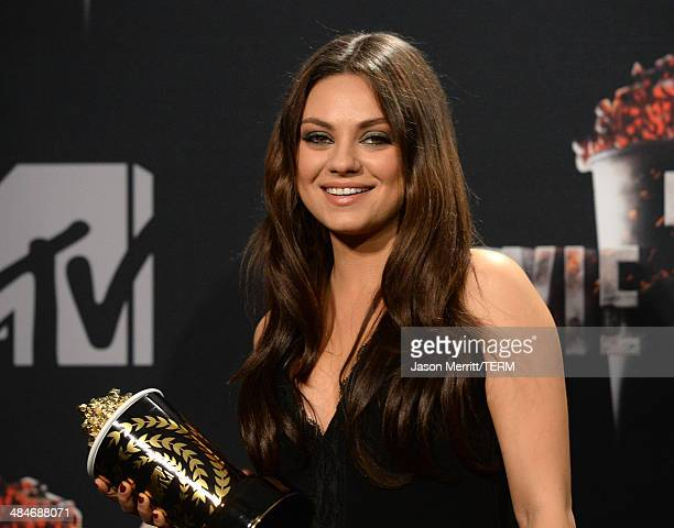 Actress Mila Kunis poses with the Best Villain award for 'Oz The Great and Powerful' in the press room during the 2014 MTV Movie Awards at Nokia...