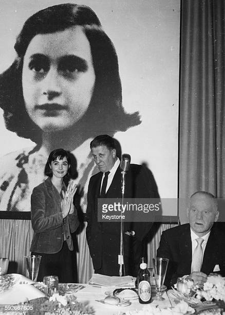 Actress Millie Perkins talking to producer George Stevens in front of a picture of holocaust victim Anne Frank at a reception for their film 'The...