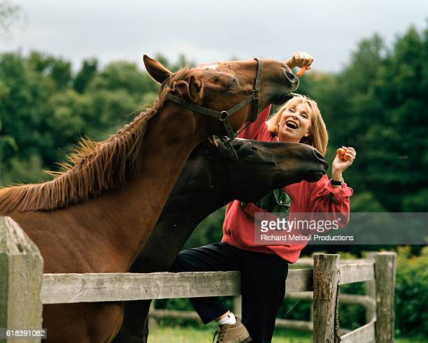 Actress Mireille Darc Feeding Horses