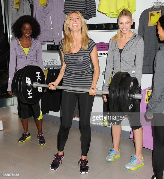 Actress Model Heidi Klum poses with models wearing her new clothing line during the Heidi Klum For New Balance Collection Launch at Lady Foot Locker...