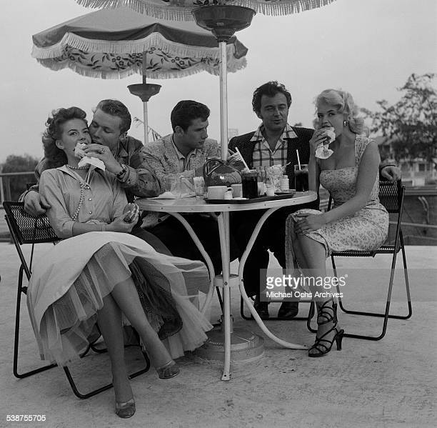 Actress Natalie Wood actor John Smith actor Bob Fuller Lance Fuller and actress Jayne Mansfield eat hamburgers at a table outside a restaurant in Los...