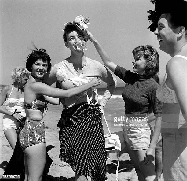 Actress Natalie Wood and Elaine Stewart dresses Jack Hailey Jr during the Thalians Beach Ball in MalibuCalifornia