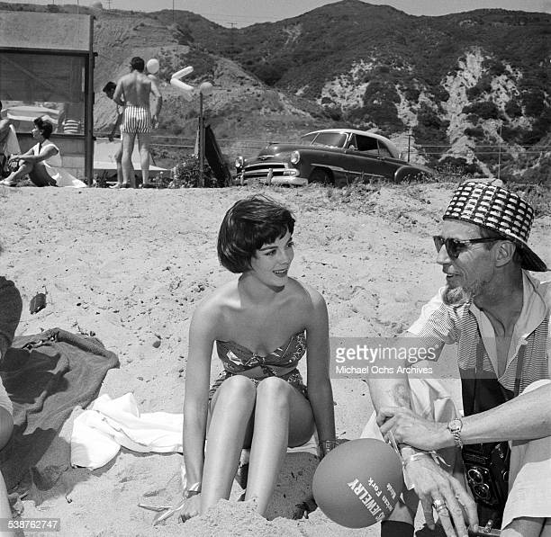 Actress Natalie Wood talks with photographer Earl Leaf during the Thalians Beach Ball in MalibuCalifornia