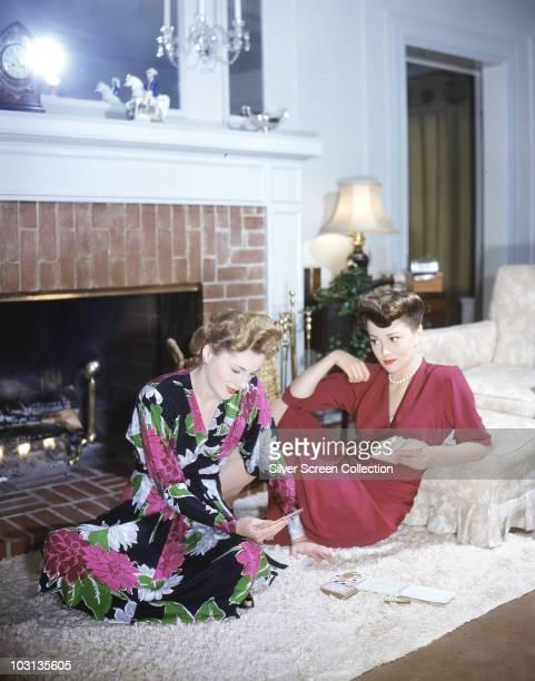 Actress Olivia de Havilland plays cards with her sister actress Joan Fontaine circa 1945