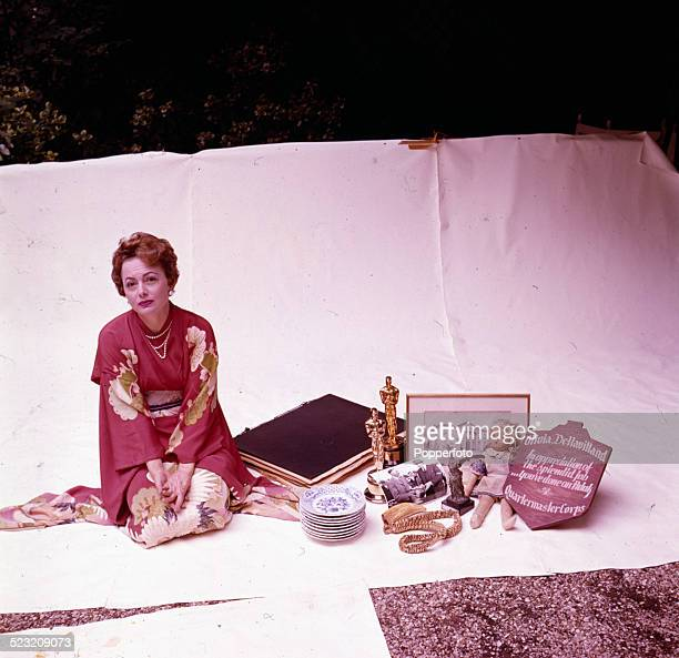Actress Olivia de Havilland posed wearing a kimono style robe surrounded with various personal items including two Academy Awards for Best Actress in...
