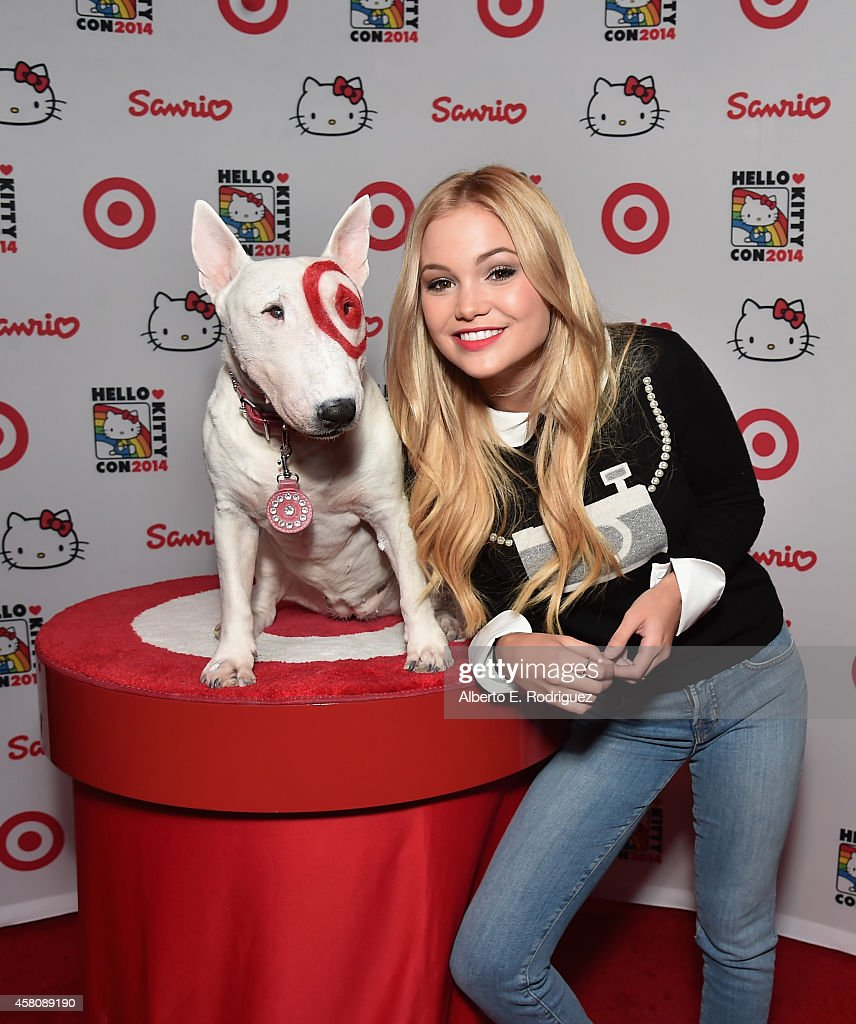Actress Olivia Holt poses with Bullseye the Target dog to Hello Kitty Con 2014 Opening Night Party Cohosted by Target on October 29 2014 in Los...
