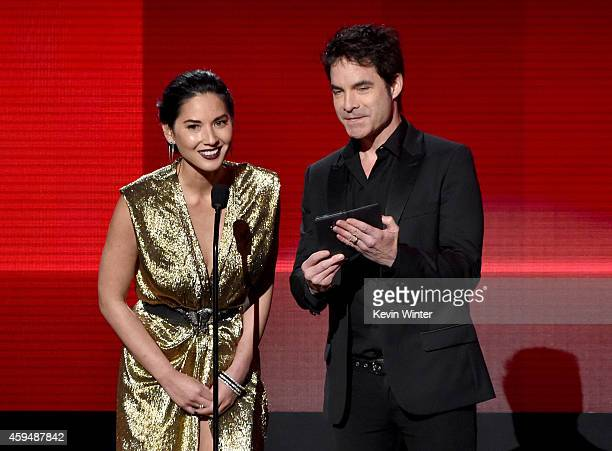 Actress Olivia Munn and recording artist Pat Monahan speak onstage at the 2014 American Music Awards at Nokia Theatre LA Live on November 23 2014 in...