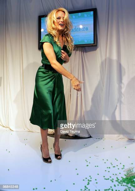 Actress Pamela Anderson appears onstage attempting to throw green MM's over the media and crowd as the bowl broke and dropped on the floor during the...