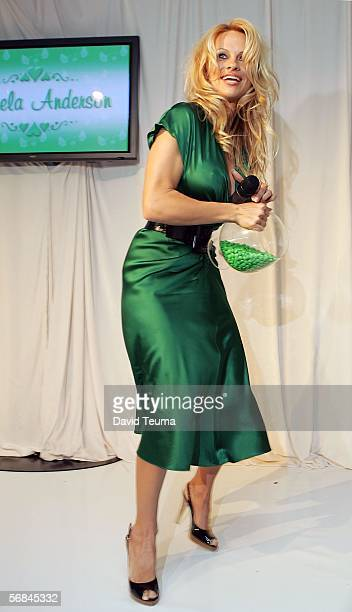 Actress Pamela Anderson enters the stage to attempt to throw green MM's over the media and crowd as the bowl broke and dropped on the floor during...