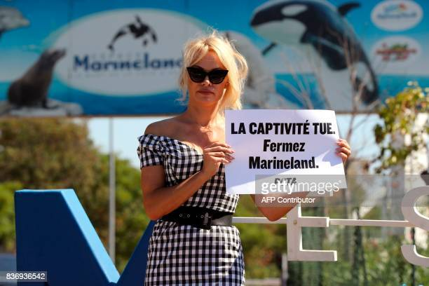 US actress Pamela Anderson holds a placard reading 'captivity kills shut Marineland' in front of French marine park Marineland during a protest of...