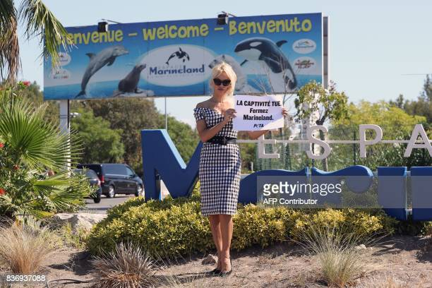 TOPSHOT US actress Pamela Anderson holds a placard reading 'captivity kills shut Marineland' in front of French marine park Marineland during a...