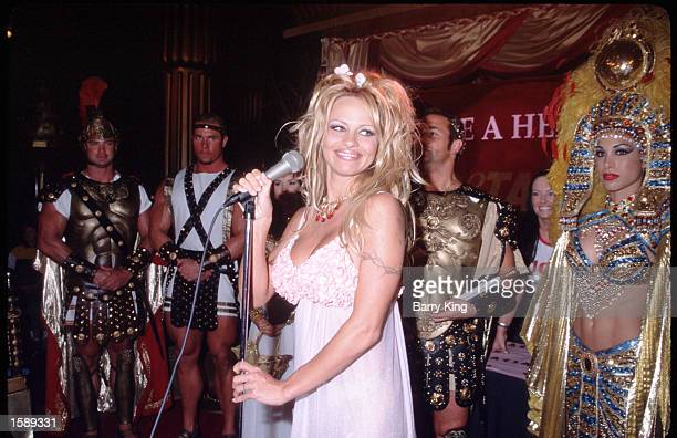 Actress Pamela Anderson Lee holds a microphone during the PETA event June 12 1999 in Las Vegas NV Anderson got her start in Labatt's beer commercials...