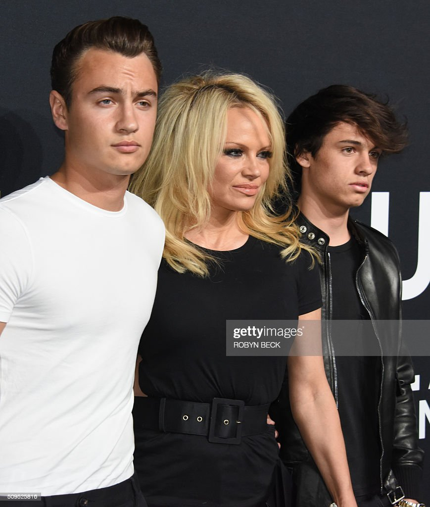 Actress Pamela Anderson (C) with her sons Brandon Lee (L) and Dylan Lee, attends the Saint Laurent men's fall line and the first part of its women's collection fashion show at the Paladium, in Hollywood, California, February 10, 2016. / AFP / ROBYN BECK
