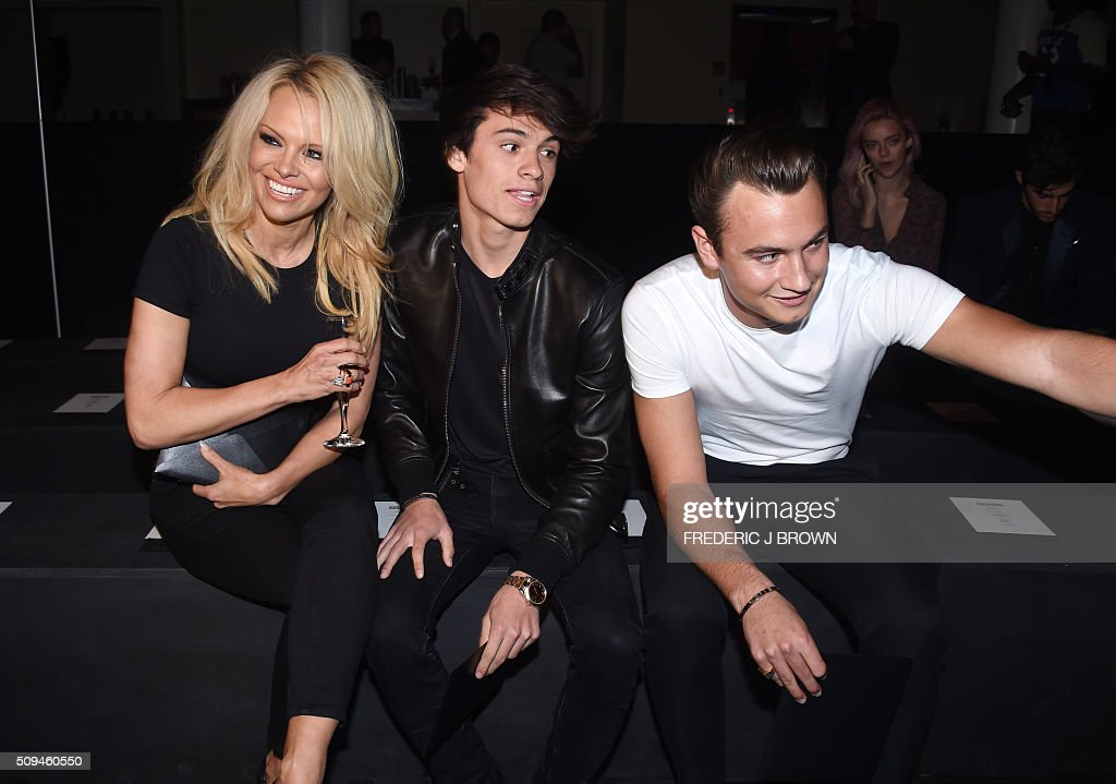 Actress Pamela Anderson with son Dylan Lee (C) and Brandon Lee (R) attend the Yves Saint Laurent men's fall line and the first part of its women's collection fashion show at the Paladium, in Hollywood, California, February 10, 2016. / AFP / FREDERIC J BROWN