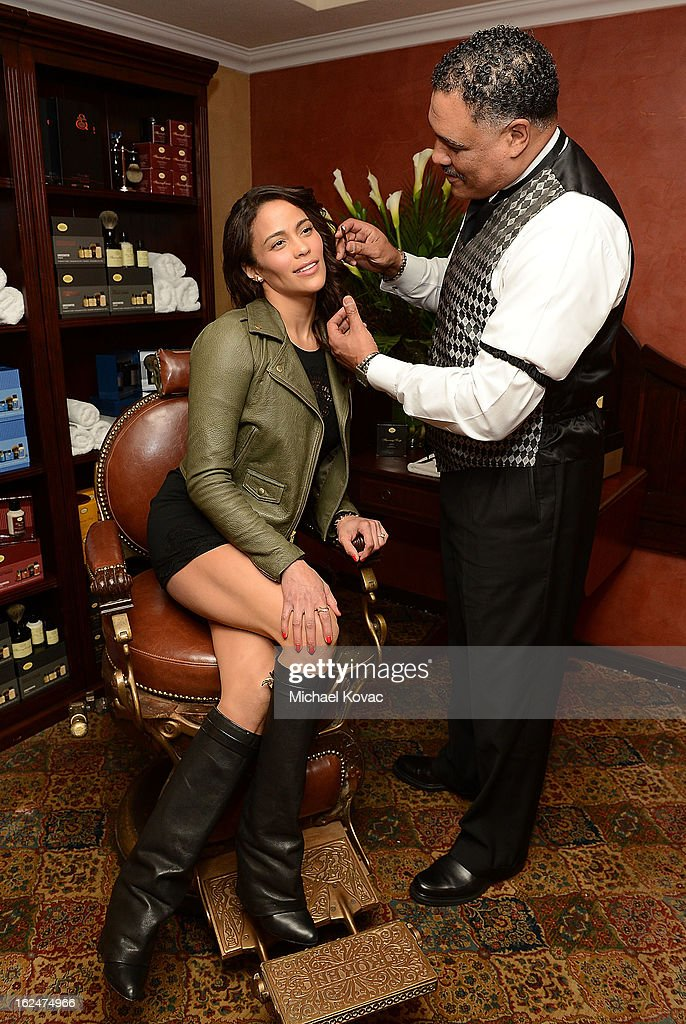 Actress Paula Patton poses with a barber at the The Art of Shaving And Bungalow 8 Pre-Oscar Party at Petit Ermitage Hotel on February 20, 2013 in West Hollywood, California.