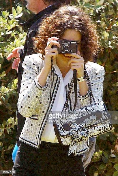 Actress Penelope Cruz takes photos of the photographers during a photocall for the film Fan Fan La Tulipe at the Palais des Festivals during the 56th...