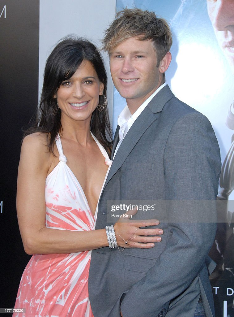 Actress Perrey Reeves (L) and guest arrive at the Los Angeles Premiere of 'Elysium' on August 7, 2013 at Regency Village Theatre in Westwood, California.
