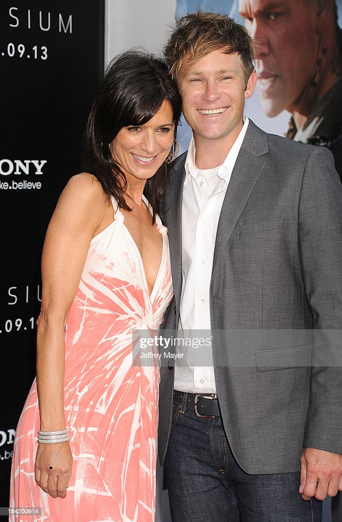 Actress Perrey Reeves and guest arrive at the Los Angeles premiere of 'Elysium' at Regency Village Theatre on August 7, 2013 in Westwood, California.