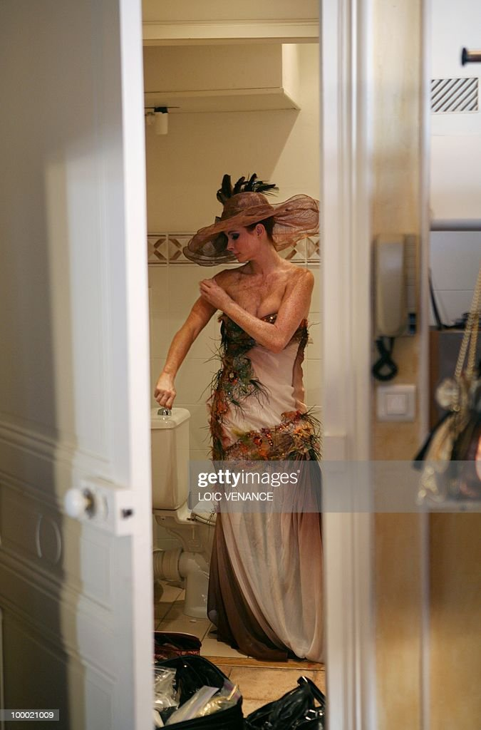 US actress Phoebe Price tries a dress designed by French Christophe Guillarme (R) as she prepares to walk on the red carpet at the 63rd Cannes Film Festival on May 20, 2010 in Cannes.