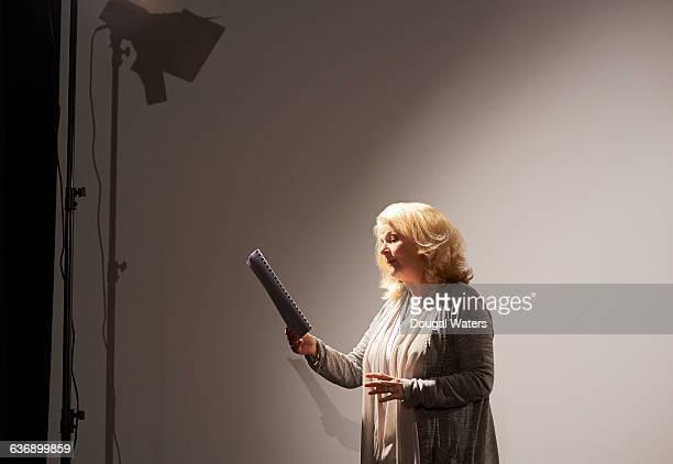 Actress rehearsing under spotlight.