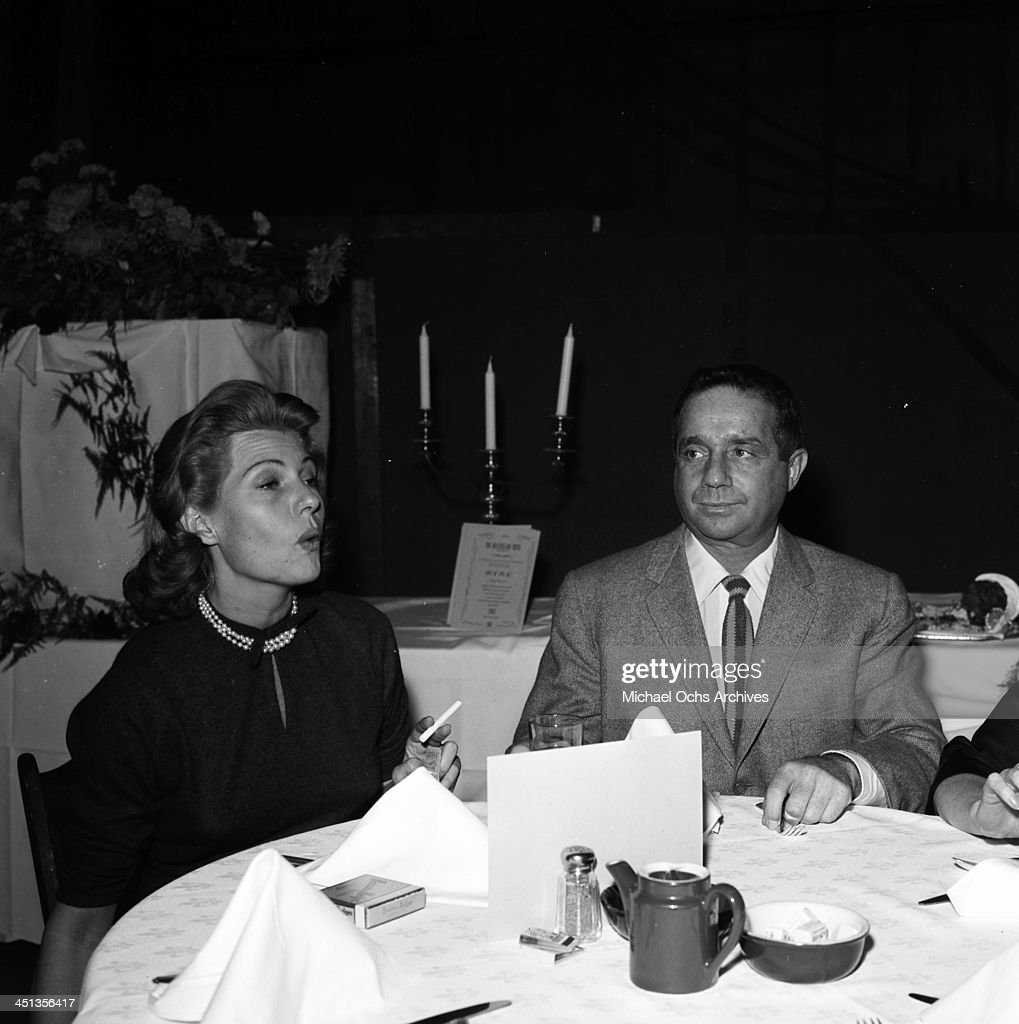 Actress Rita Hayworth sits with Jim Hill at a party in Los Angeles California