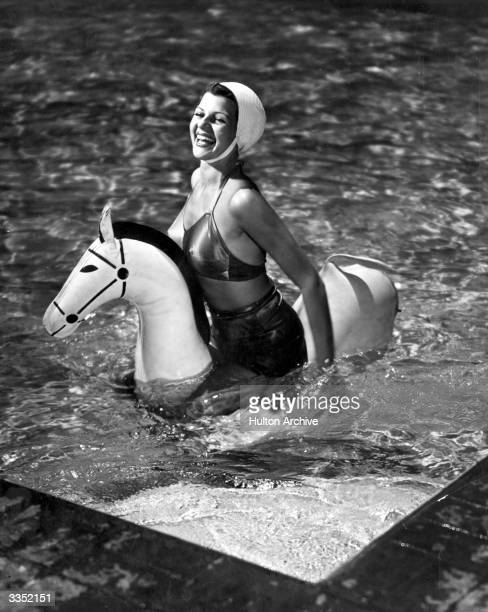 Actress Rita Hayworth swims with an inflatable horse on a break between filming