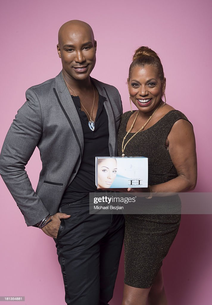 Actress Rolanda Watts (R) gets a gift from Marc Harvey of 'Element 2 Beauty' at the Mark Kearney Group 'Iced Out' Luxury Emmy Suite on September 19, 2013 in Los Angeles, California.