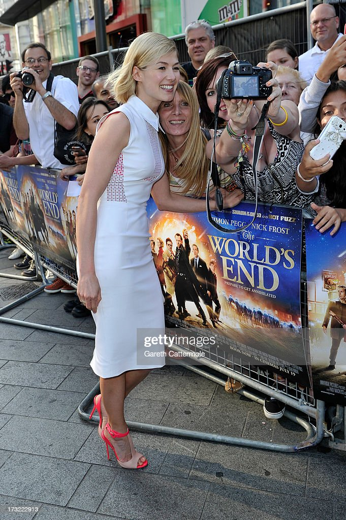 Actress Rosamund Pike signs autographs for fans as she arrives at the World Premiere of The World's End at Empire Leicester Square on July 10, 2013 in London, England.