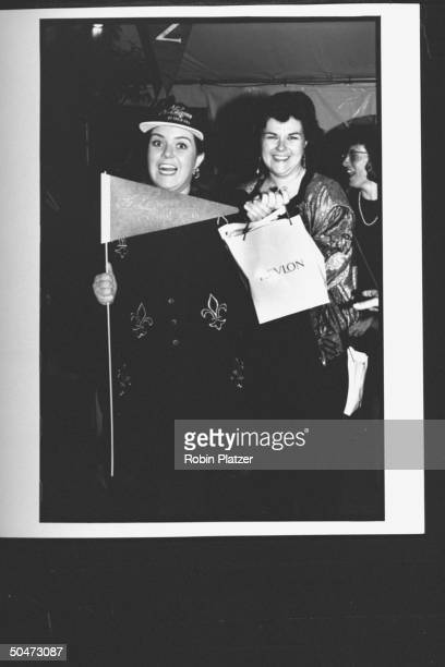 Actress Rosie O'Donnell wearing baseball cap holding pennant w unident woman at premiere party for the movie A League of Their Own at Tavern on the...