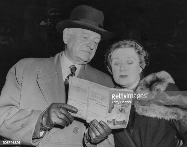 Actress Ruby Miller and publicist W J MacQueenPope reading a program for the play 'The Orchid' which first opened in 1903 at the filming of the...