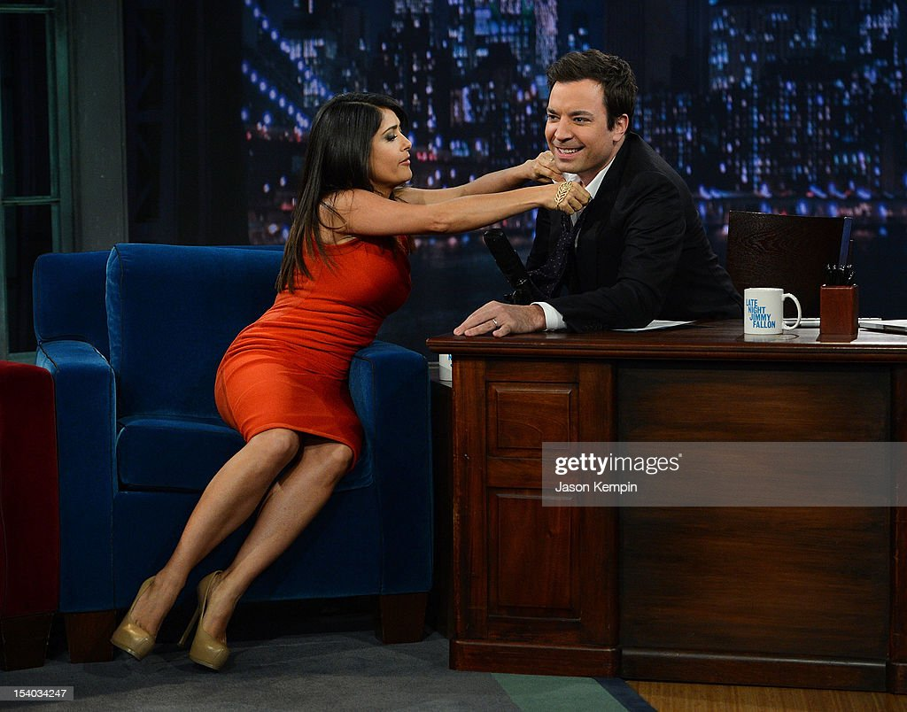 Actress Salma Hayek Pinault helps host Jimmy Fallon with his tie during a taping of 'Late Night With Jimmy Fallon' at Rockefeller Center on October 12, 2012 in New York City.
