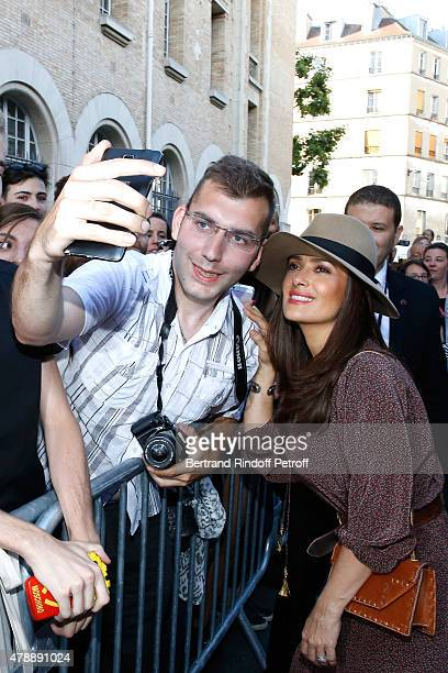 Actress Salma Hayek signs autographs as she arrive at the Saint Laurent Menswear Spring/Summer 2016 show as part of Paris Fashion Week on June 28...