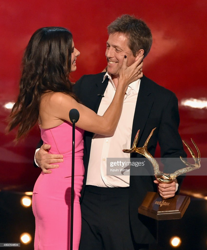 Actress Sandra Bullock accepts the Decade of Hotness award from actor Hugh Grant onstage during Spike TV's 'Guys Choice 2014' at Sony Pictures Studios on June 7, 2014 in Culver City, California.