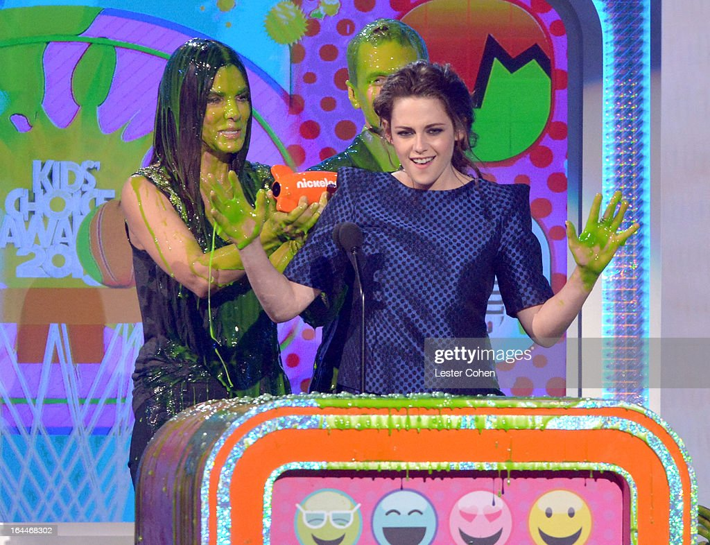 Actress Sandra Bullock (L) and actress Kristen Stewart perform during Nickelodeon's 26th Annual Kids' Choice Awards at USC Galen Center on March 23, 2013 in Los Angeles, California.