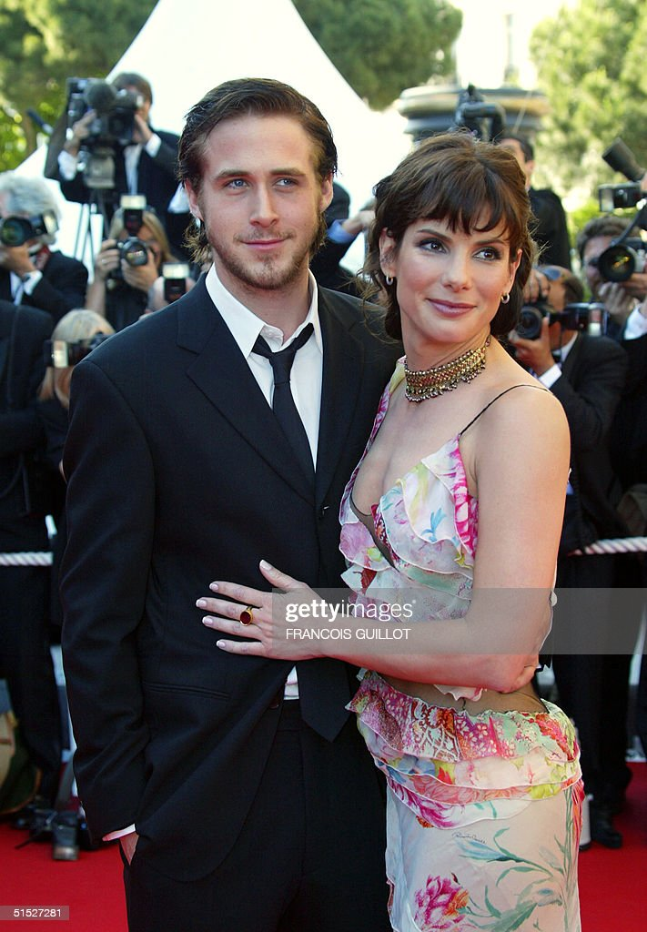 US actress Sandra Bullock poses for photographers with actor Ryan Gosling as they arrive at the palais des festivals to attend the screening of their...