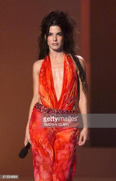 Actress Sandra Bullock walks onto the stage in a bright orange dress at the 1999 VH1/Vogue Fashion Awards 05 December 1999 in New York She introduced...