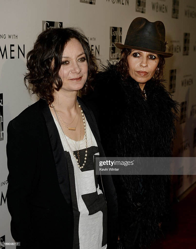 Actress <a gi-track='captionPersonalityLinkClicked' href=/galleries/search?phrase=Sara+Gilbert&family=editorial&specificpeople=585732 ng-click='$event.stopPropagation()'>Sara Gilbert</a> (L) and her partner producer/musician <a gi-track='captionPersonalityLinkClicked' href=/galleries/search?phrase=Linda+Perry&family=editorial&specificpeople=2133172 ng-click='$event.stopPropagation()'>Linda Perry</a> arrive at An Evening With Women benefiting The L.A. Gay & Lesbian Center at the Beverly Hilton Hotel on May 18, 2013 in Beverly Hills, California.
