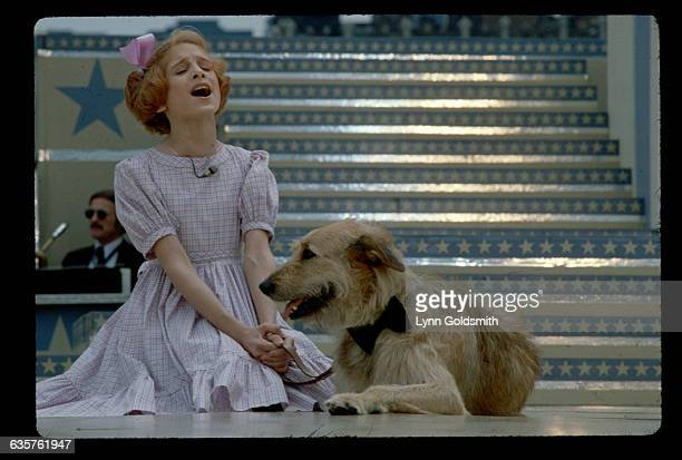 Actress Sarah Jessica Parker performs a scene with a dog in the musical Annie