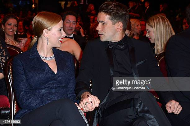 Actress Scarlett Johansson and Romain Dauriac sit in the audience before the start of the 39th Cesar Film Awards 2014 at Theatre du Chatelet on...