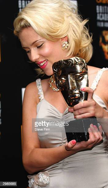 Actress Scarlett Johansson poses with her award in the pressroom at 'The Orange British Academy Film Awards' at The Odeon Leicester Square on...