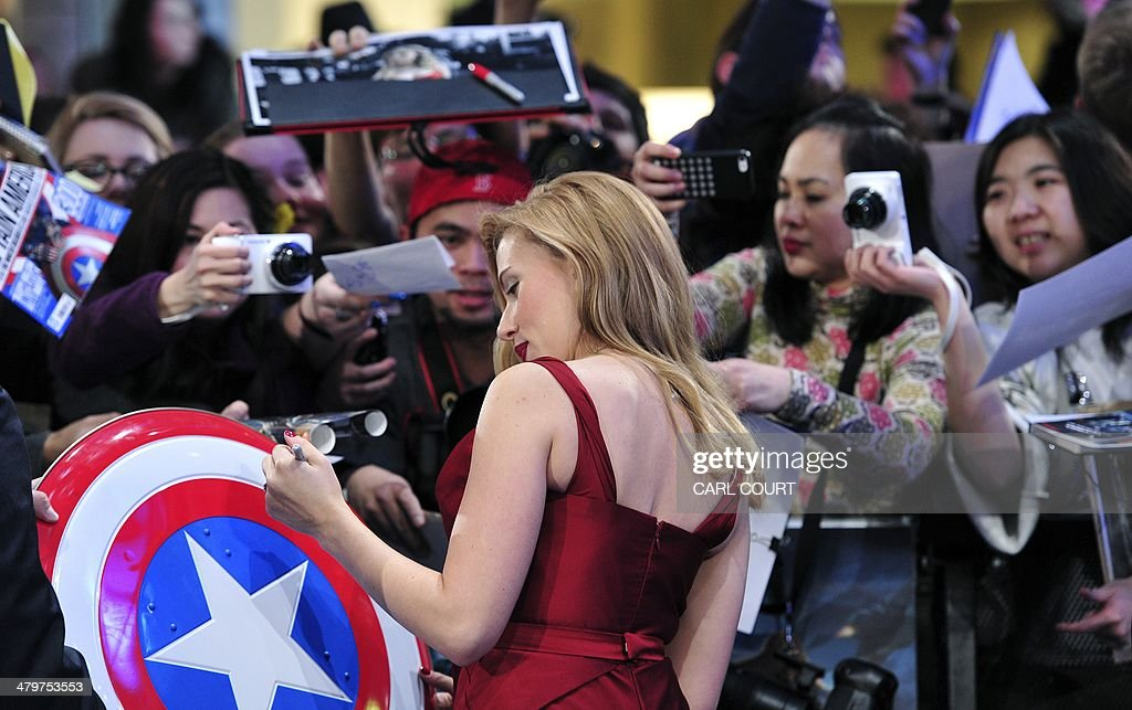 US actress Scarlett Johansson signs autographs as she arrives to attend the UK premiere of Captain America: The Winter Soldier in London on March 20, 2014. AFP PHOTO / CARL COURT