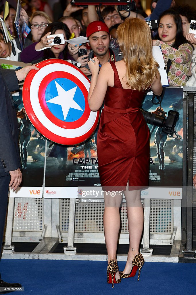 Actress Scarlett Johansson signs autogtraphs as she attends the UK Film Premiere of 'Captain America: The Winter Soldier' at Westfield London on March 20, 2014 in London, England.
