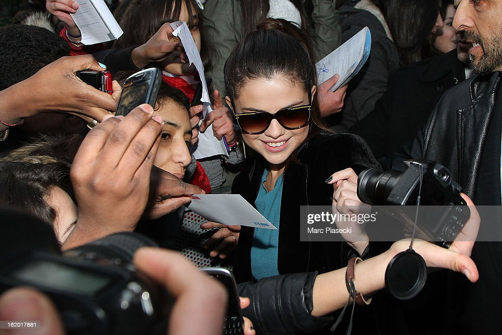 Actress <a gi-track='captionPersonalityLinkClicked' href=/galleries/search?phrase=Selena+Gomez&family=editorial&specificpeople=4295969 ng-click='$event.stopPropagation()'>Selena Gomez</a> signs autographs as she leaves the 'NRJ' radio station on February 18, 2013 in Paris, France.