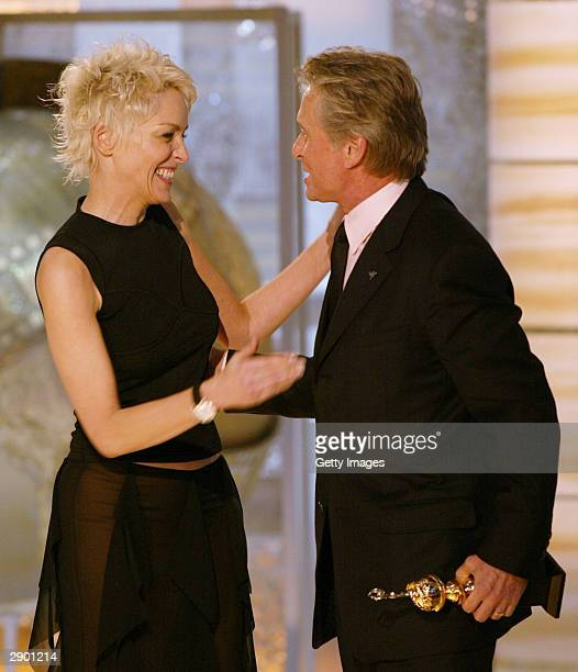 Actress Sharon Stone and Winner of the Cecil B DeMille Award Michael Douglas on stage at the 61st Annual Golden Globe Awards on January 25 2004 at...