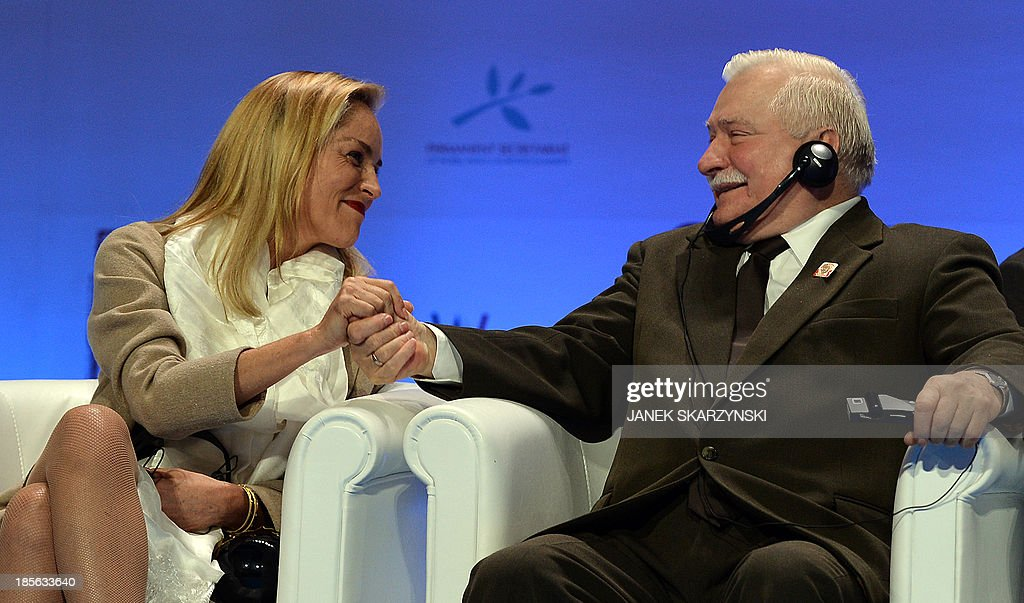 US actress Sharon Stone (L) shakes hands with Former Polish President and 1983 Nobel Peace laureate Polish Lech Walesa after she received the Peace Summit Award at the end of the World Summit of Nobel Peace Laureates on October 23, 2013 in Warsaw. AFP PHOTO/JANEK SKARZYNSKI