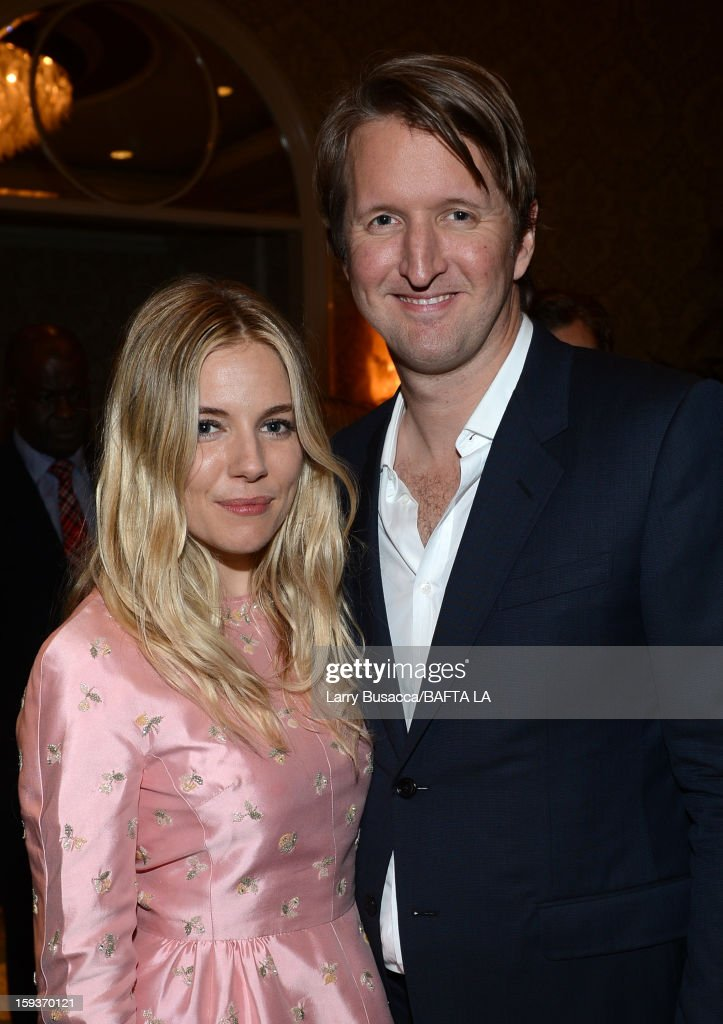 Actress <a gi-track='captionPersonalityLinkClicked' href=/galleries/search?phrase=Sienna+Miller&family=editorial&specificpeople=171883 ng-click='$event.stopPropagation()'>Sienna Miller</a> and director <a gi-track='captionPersonalityLinkClicked' href=/galleries/search?phrase=Tom+Hooper&family=editorial&specificpeople=681836 ng-click='$event.stopPropagation()'>Tom Hooper</a> arrive at the BAFTA Los Angeles 2013 Awards Season Tea Party held at the Four Seasons Hotel Los Angeles on January 12, 2013 in Los Angeles, California.