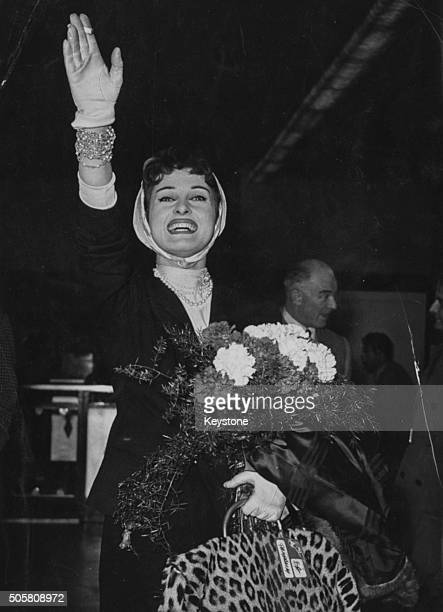 Actress Silvana Pampanini holding a bouquet of flowers and waving as she arrives home after attending Tokyo Film Festival at Ciampino Airport in Rome...