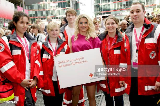 Actress singer Jeanette Biedermann pose with members of red cross at the Fan Event of 'Anna Und Die Liebe' and 'Hand aufs Herz' at Sony Centre on May...